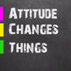 Hand writing Attitude Changes Things with white chalk on blackboard background.